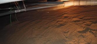 Een frisse nieuwe zandlaag gespoten over de vochtige en vieze kruipruimtebodem