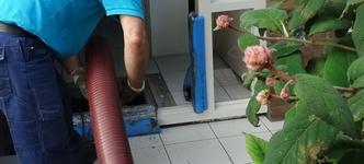 Een medewerker gaat de kruipruimte in, terwijl een andere medewerker de blaasapparatuur bedient